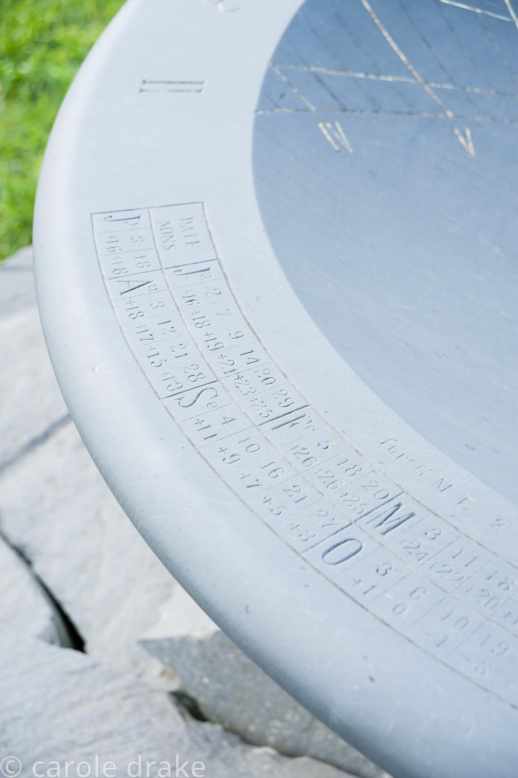 Slate sundial measuring 1.5m in diameter, designed by Sir Mark Lennox-Boyd. It emulates the earliest known sundial dating fro...