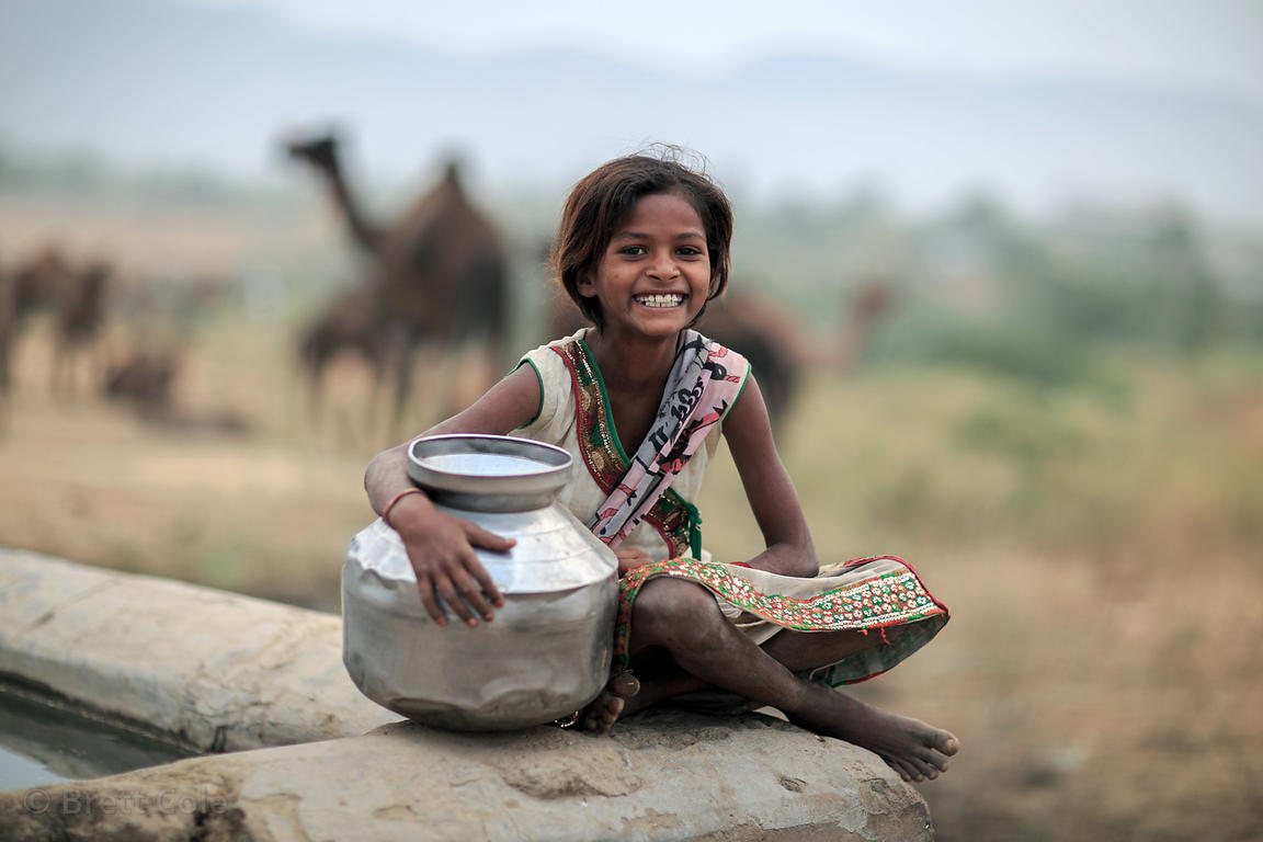 Happy girl collecting water from a trough during the Pushkar Camel Fair, Pushkar, Rajasthan, India