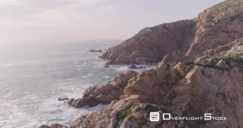Aerial drone flying by the rocky coast with waves crashing on the rocks of Portugal