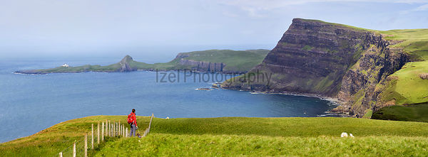 A hiker and their dog on the sea cliffs of Ramasaig with Neist Point in the distance. Isle of Skye, Scotland, UK.