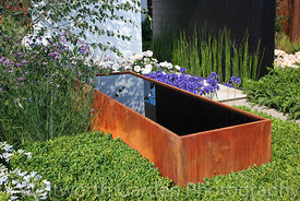 Corten steel water trough below a tiled pavilion with planting of Buxus sempervirens, Agapanthus, Equisetum hyemale, Verbena ...