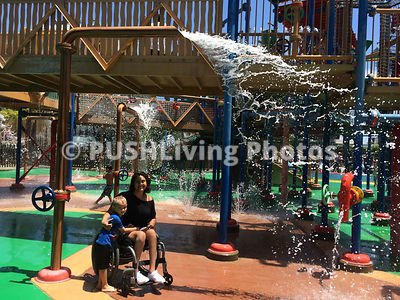 Young mother in a wheelchair with her son at a water park