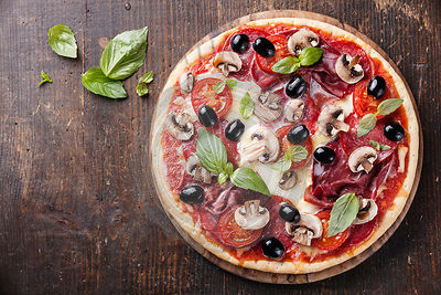 Italian pizza with salami, mushrooms and olives on wooden table