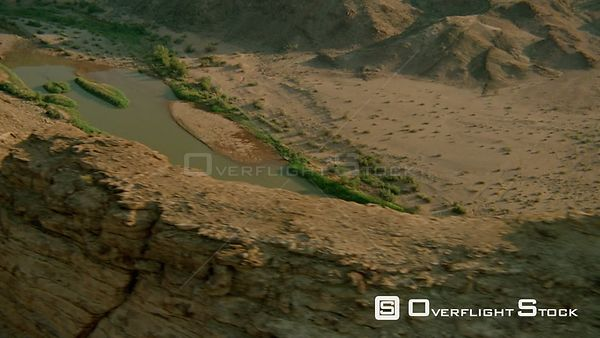 Aerial wide angle shot rocky formations and wide river with green vegetation on both sides Fish River Canyon Namibia