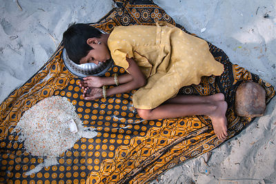 A girl falls asleep clutching a coin while panhandling for money or rice (left) at the Gangasagar Mela, a Hindu pilgrimage to...