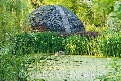 Dome structure made of thousands of bottles seen beyond lake and Iris pseudacorus var. bastardii. Westonbury Mill Water Garde...