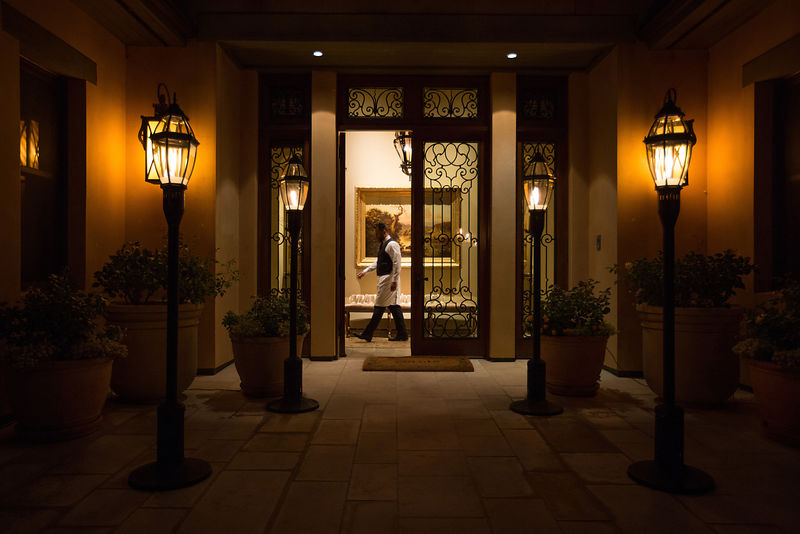 "A server passes an open doorway during a break in dinner service. Photo ©2017 by <a href=""http://www.tinacciphoto.com"">Jason Tinacci</a> / Napa Valley Vintners"