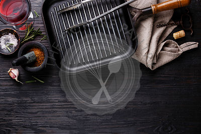 Empty frying pan, seasonings and red wine on black burned wooden background copy space