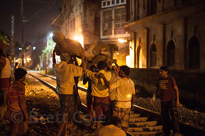 Workers carry an idol at night in Kumartoli (Potter's Town), Kolkata, India.