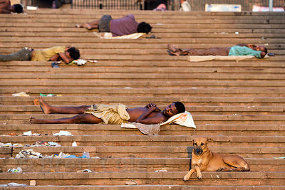 Homeless people sleep on the steps of Jama Masjid mosque at sunrise on a hot September morning, Delhi, India