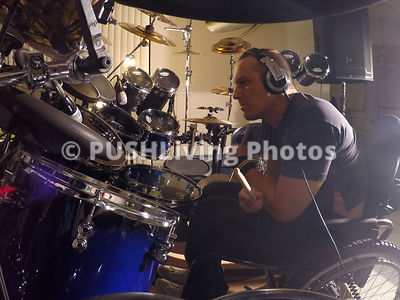 Man in a wheelchair in a music studio with a drum kit