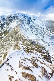 Two hikers in the distance approaching Helvellyn from Striding Edge.
