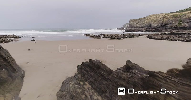 Low flying aerial drone flying over rocks jetting out of the sand of an empty beach off the coast of Portugal