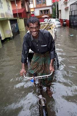 A rickshaw driver plies his trade during monsoon flooding, Lake Gardens, Kolkata, India. Taken during the heaviest rains in K...