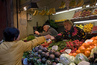 Italy - Bologna - Women buying vegetables at a stall in the Mercato di Mezzo