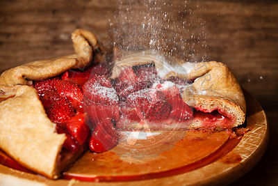 Strawberry pie and powdered sugar on wooden background