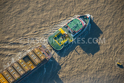 Barge pulling containers of rubbish on the River Thames, London.