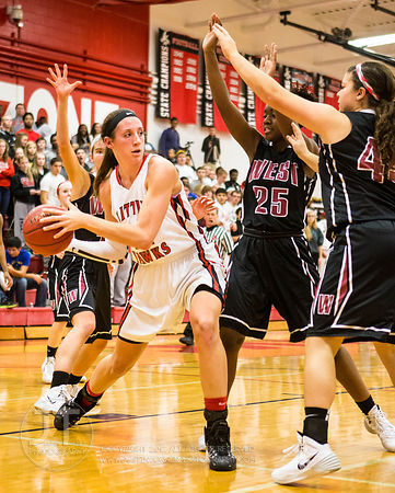 Iowa City High's Hayley Lorenzen (44) looks to pass around Waterloo West's Makayla Stokes (25) and Blaire Thomas (43) at the ...