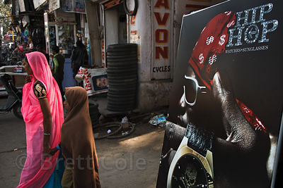 Woman and daughter in conservative dress walk past an ad for Hip-Hop watches, Bharatpur, Rajasthan, India