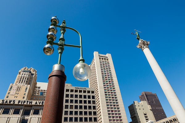 Column and buildings in Union Square against blue sky in San Francisco, USA