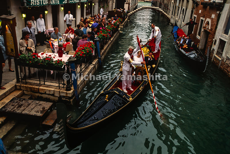 Spectators at a restaurant watch a bride and groom in a gondola after their wedding. Venice, Italy, 1993.