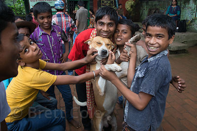 Children play with a street dog at a shelter for homeless or otherwise at-risk boys at Sealdah Station, Kolkata, India