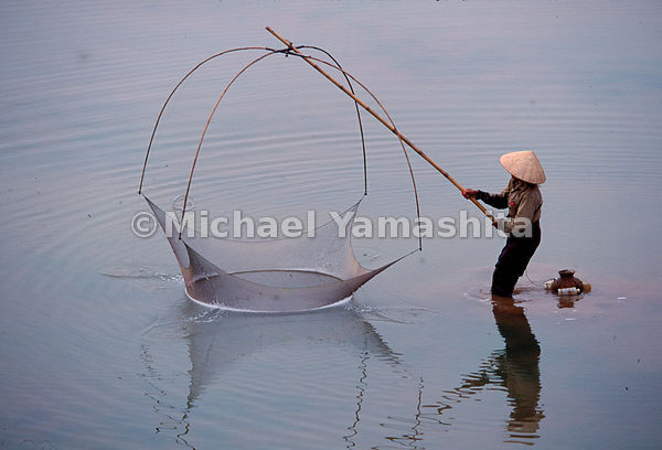 A woman practices the ancient art of dip-net fishing in the shallow water along the banks on Vientiane, Laos' sleepy capital ...