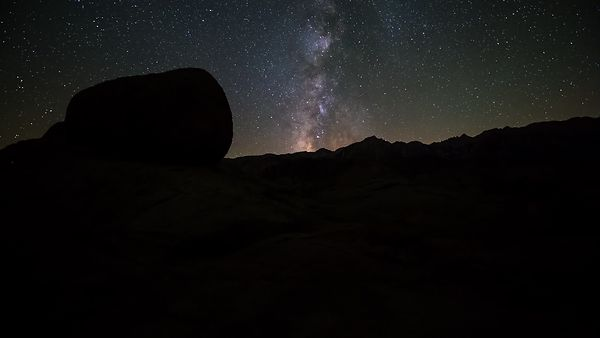 Medium Shot: Dolly Shot Following The Sierra Mountain Range Under A Milky Way & Moon Strike