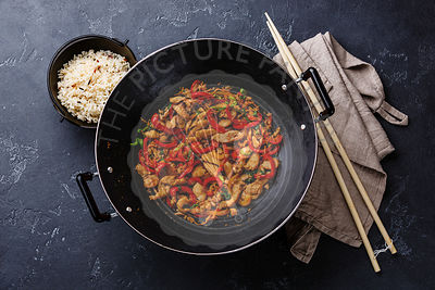 Stir-fry with chicken meat and vegetables in Wok pan on dark stone background