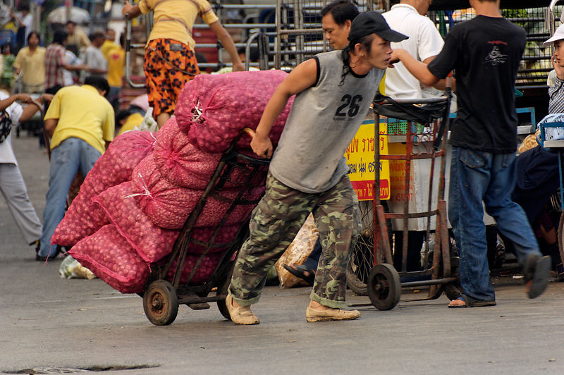 Market porter carrying chillies on trolley, Pak Klong Dalat market, Bangkok, Thailand.
