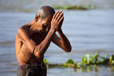A man prays in the Hooghly River at Sovabazar Ghat, Kolkata, India.
