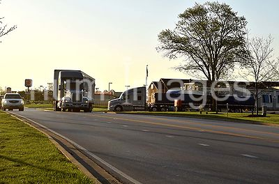 Two Semi-trucks (18 wheelers) leaving a truck stop entering a road
