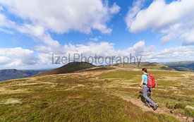 A female hiker walking a narrow trail towards the summit of Great Borne with Starling Dodd behind. The English Lake District, UK.