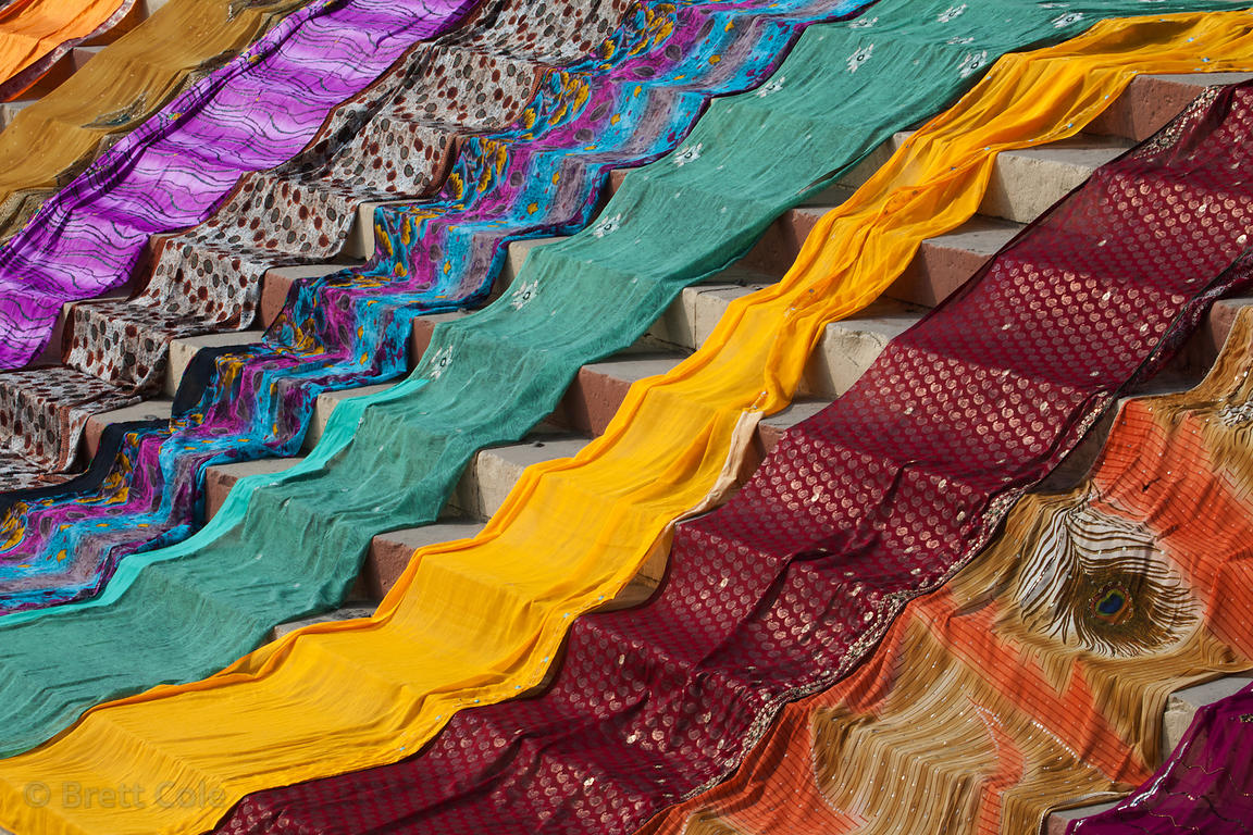 Colorful saris dry along the Ganges River near Lal Ghat, Varanasi, India.