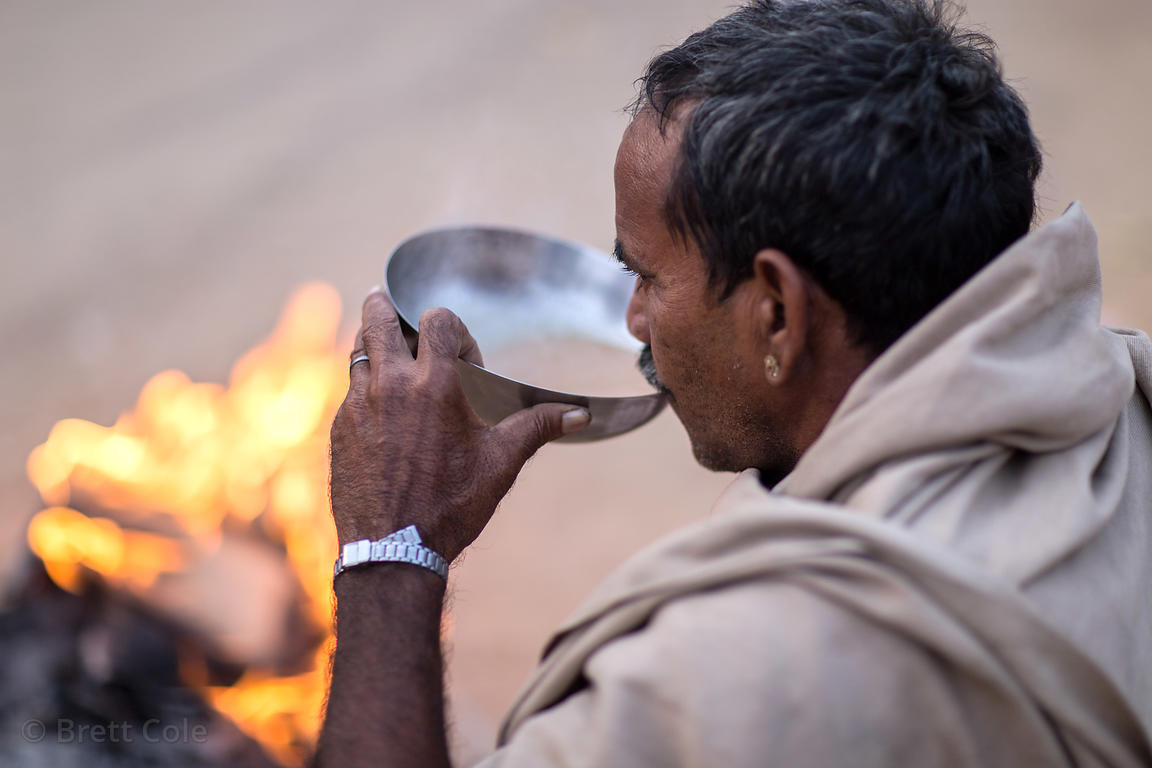A man drinks chai tea from a metal pan while warming to a fire on a cold winter morning in Pushkar, Rajasthan, India