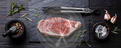 Raw fresh meat Steak Striploin and seasonings on black burned wooden background copy space