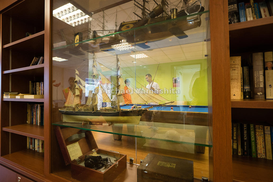 Standing proud on a glass shelf overlooking the recreation room, an ornate miniature model of a mariner's sailing ship pays h...