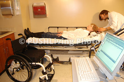 Woman in a wheelchair in an examination room with her doctor