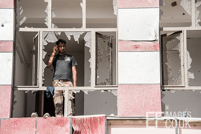 An Iraqi Army Soldier talks on his phone behind the blown out windows of a building in West Mosul. Iraq, 5th June 2017