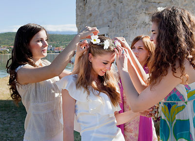 Women placing daisy crown on bride