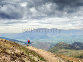 A hiker and their dog walking down from the summit of Sail with Skiddaw in the distance. English Lake District, UK.