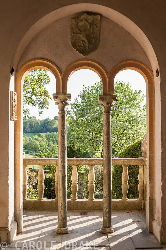 View through columns and over the balcony across surrounding countryside.  Iford Manor, Bradford-on-Avon, Wiltshire