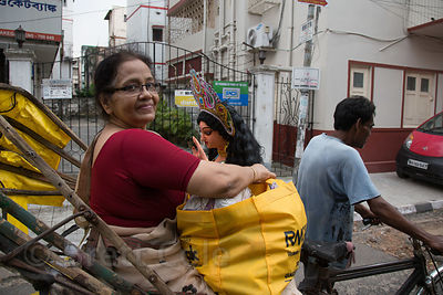 A woman carries an idol in a rickshaw during the Durga Puja festival, Lake Gardens, Kolkata, India