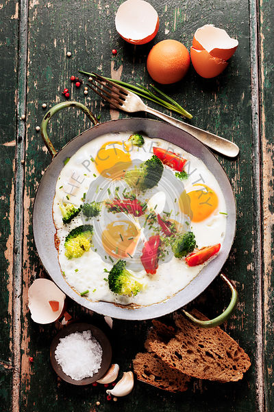 Pan of fried eggs, broccoli and cherry-tomatoes with bread on old green background, top view
