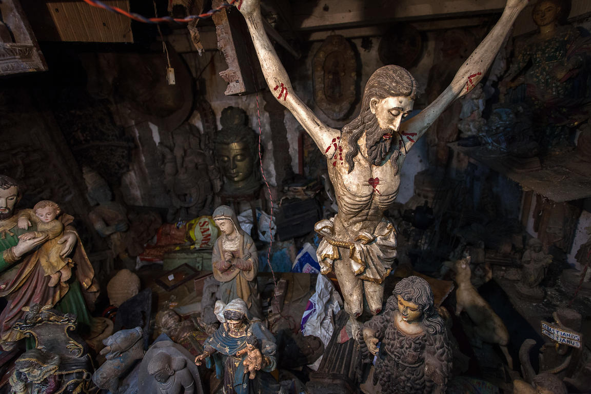 A wooden figure of Jesus on the cross, among other religious figures, in the dusty backroom of a shop at Chor Bazaar, also kn...