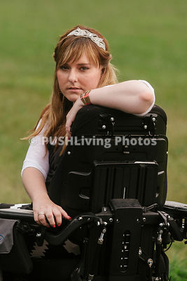 Young woman in a power wheelchair enjoying her home garden