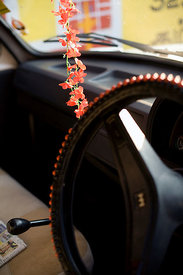 India - Swamimalai - A garland of flowers hang from the mirror of an Hindustan Ambassador  car