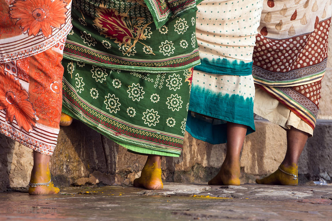 Women bathe in the Ganges River. Their feet are yellow because they've been covered in Turmeric to prevent infection from the...