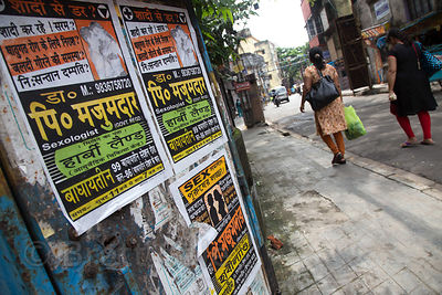 "Women walk past a sign for ""Government Registered Sexologist"" services, Lake Gardens, Kolkata, India"