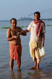 A man receives blessings along the Hooghly River, Kolkata, India. In the background is a large leather factory.